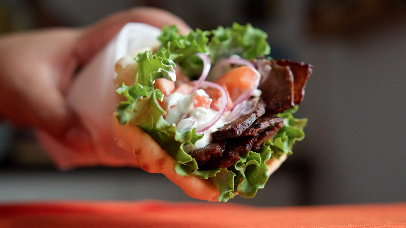 An image of a gyro, a Greek sandwich with pita, lettuce, tomato, onion and meat made in Taste & Sabor, in the Kingsbridge section of Bronx, NY.
