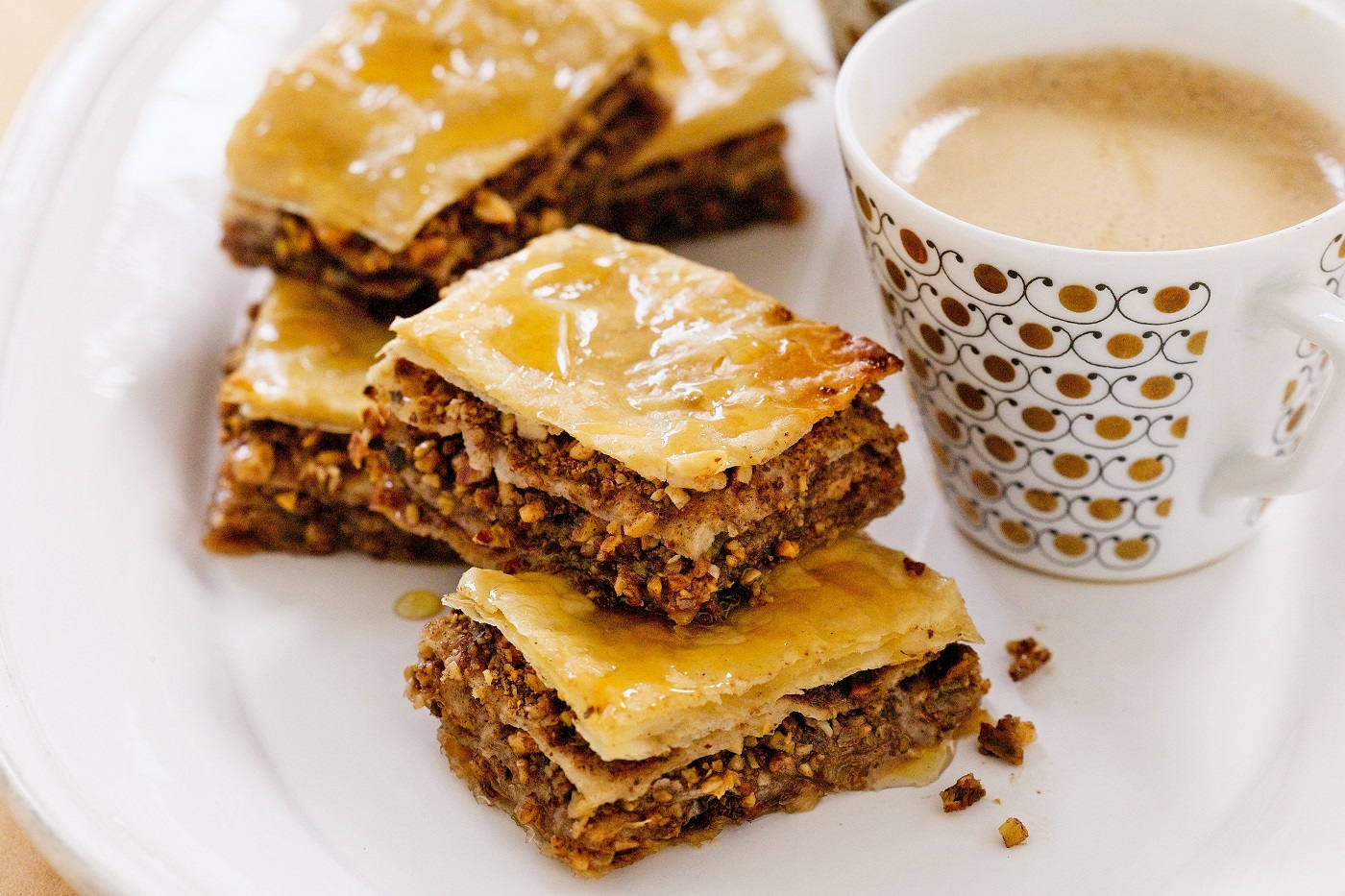 An image of a Greek Dessert called Baklava, with a cup of coffee.