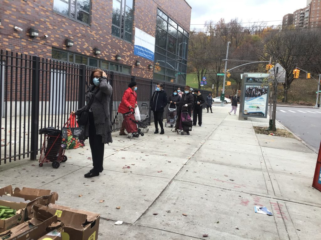 people lining on a street corner to receive fruits vegetables during food drive